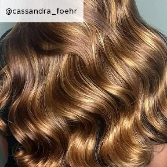 Back of woman's head with golden brown, wavy hair, created using Wella Professionals.