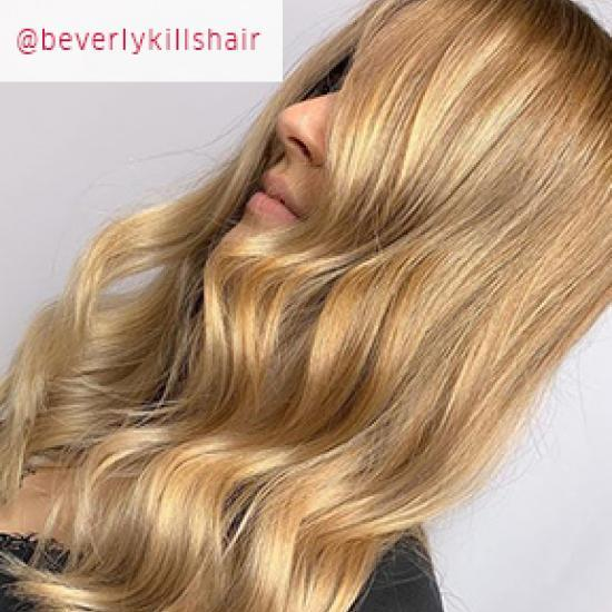 Side profile of woman with long, honey blonde, wavy hair, created using Wella Professionals.