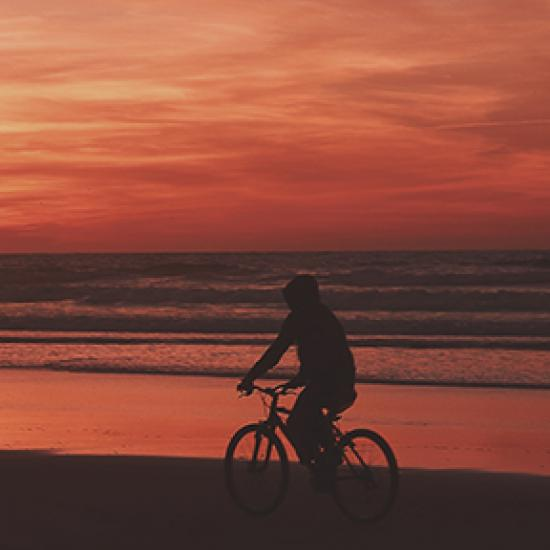Man on bike in front of red sky