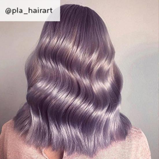 Back of woman's head with mid-length, wavy, lilac hair, created using Wella Professionals.