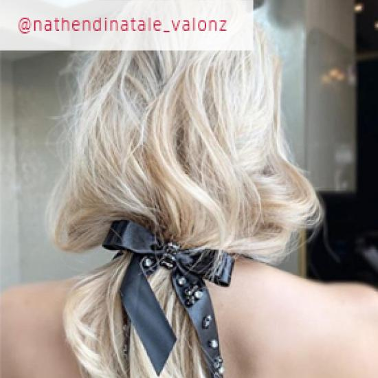 Back of womans head with pearl blonde hair in a black ribbon bow