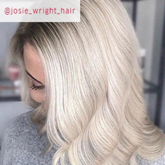 Close up image of woman facing down with curled pearl blonde hair