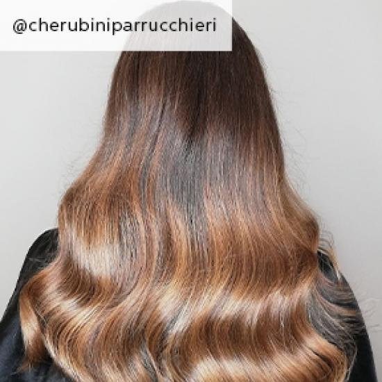 Back of woman's head with long, wavy, light brown sombre hair, created using Wella Professionals.