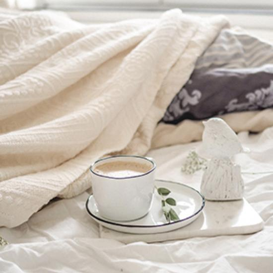 Image of coffee on cream bed sheets