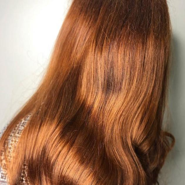 Photo of the back of a woman's head with mid-length, loose waves and pumpkin spice hair color, created using Wella Professionals.