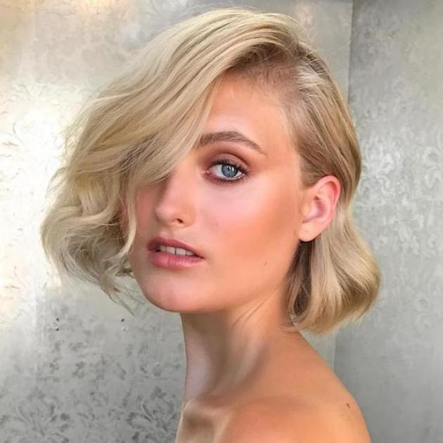 Photo of woman with blonde hair styled in a short, side-swept, wavy bob, created using Wella Professionals