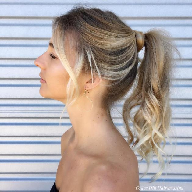Woman with long golden blonde hair, styled in a ponytail with loose waves