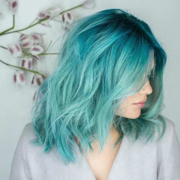 Woman with short, aqua blue hair with loose waves