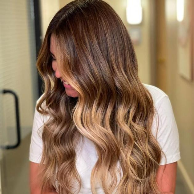 Side profile of woman with long, wavy brown hair and a blonde dip-dye, created using Wella Professionals.