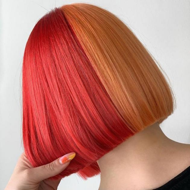 Back of woman's head with half and half hair color in orange and red, created using Wella Professionals.