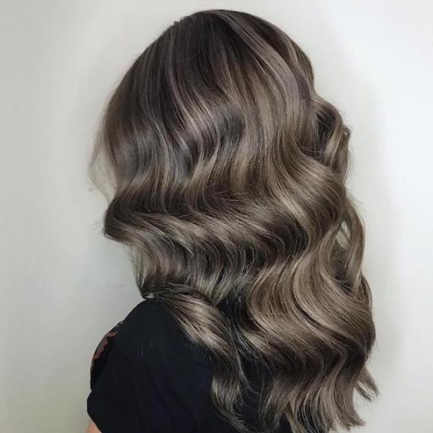 Back of woman's head with dark brown hair and gray highlights, created using Wella Professionals.