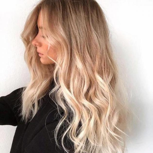Side profile of woman with long, wavy, blonde hair and highlights, created using Wella Professionals