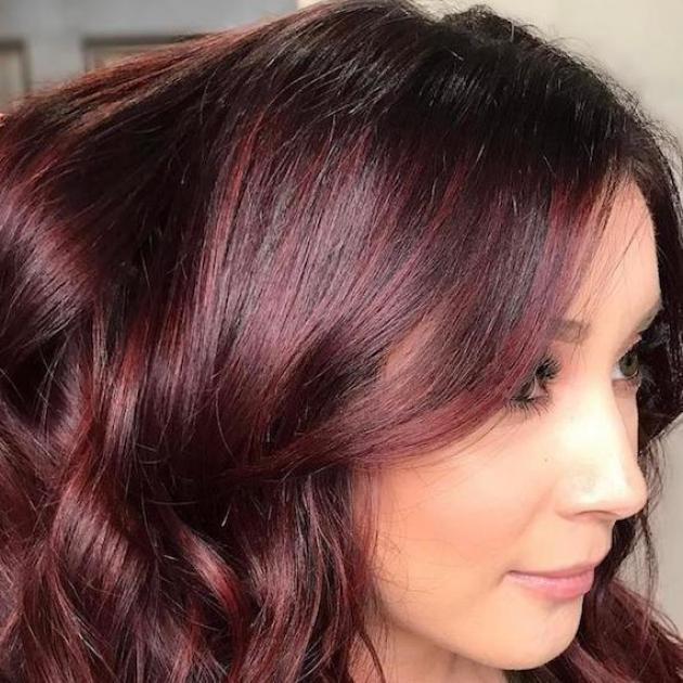 Woman with loosely curled, shiny, mahogany hair, created using Wella Professionals.