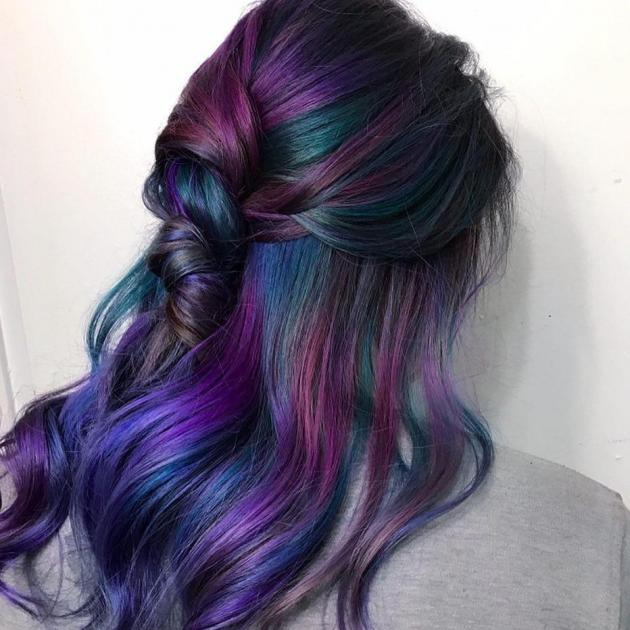 Woman with rainbow hair, half up half down hair styled with loose waves