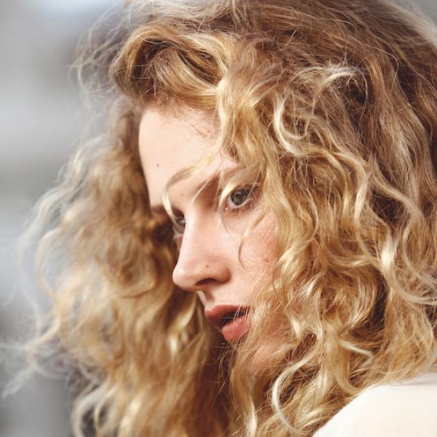 Model with blonde wavy hair blowing in the wind, created using Wella Professionals