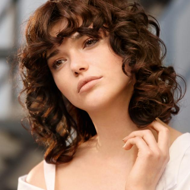 Woman with brown curly perm with fringe