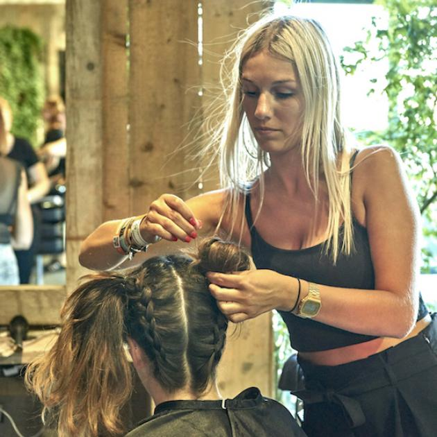Hairstylist doing plaits on a client
