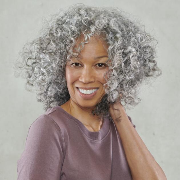 Woman facing the camera and smiling as she clutches her grey, curly hair.