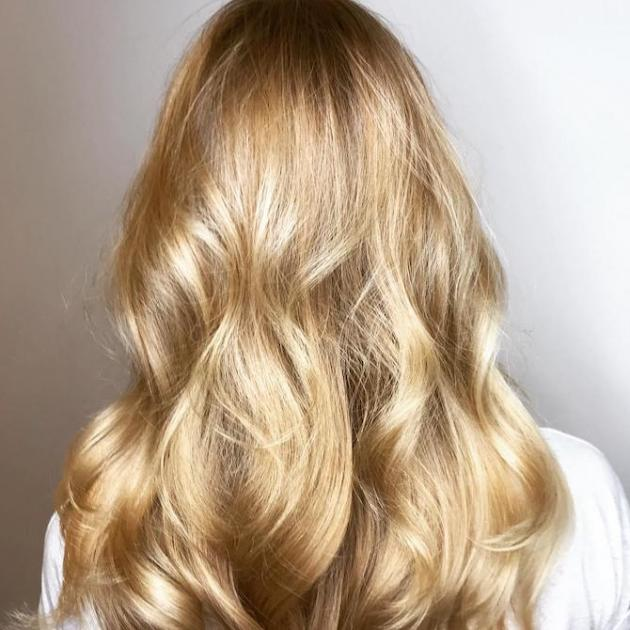 Back of woman's head with long warm blonde hair and babylights, created using Wella Professionals.