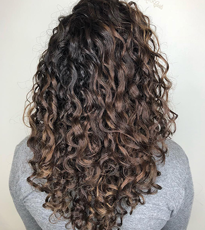 Curly ash brown balayage, created using Wella Professionals