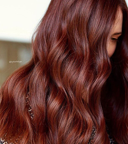 Woman with long, wavy, rich auburn hair, created using Wella Professionals.