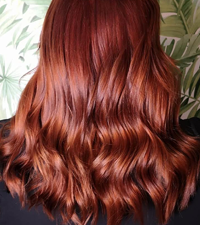 Back of woman's head with long, loosely curled, glossy auburn hair, created using Wella Professionals.