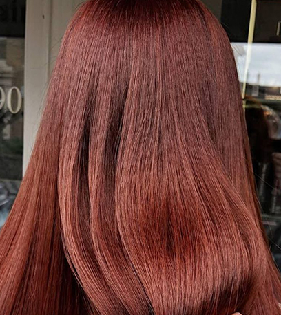 Back of woman's head with long, straight, muted auburn hair, created using Wella Pro-fessionals.