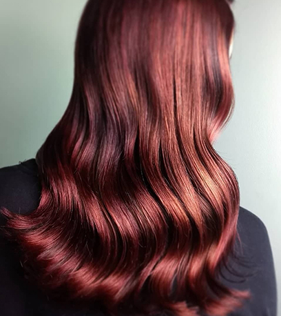Back of woman's head with long, loosely-curled, chestnut auburn hair, created using Wella Professionals.