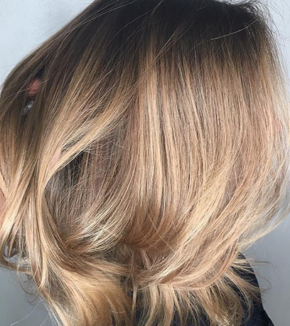 Side profile of woman with glossy, straight, golden balayage bob, created using Wella Professionals.