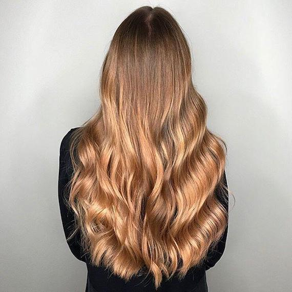 Model with long, wavy hair and warm blonde balayage, created using Wella Professionals.