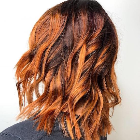Model with wavy, pumpkin spice hair and balayage, created using Wella Professionals.