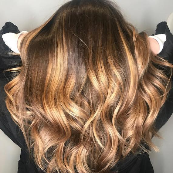 Model with long, wavy hair and caramel balayage, created using Wella Professionals.
