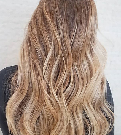 Photo of the back of a woman's head with subtle blonde balayage, created using Wella Professionals.
