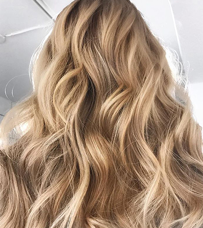 Photo of the back of a woman's head with long, soft champagne blonde hair, created using Wella Professionals.