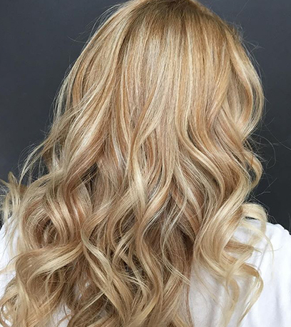 Photo of the back of a woman's head with warm blonde highlights, created using Wella Professionals.