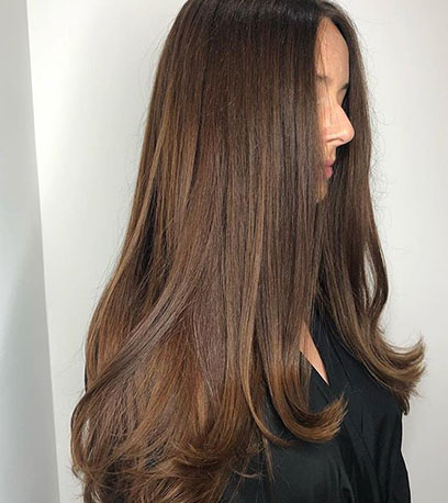 Alt tag: Woman with long, sleek brown hair, created using Wella Professionals