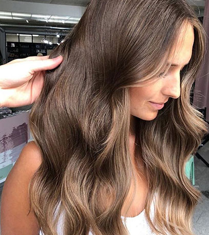 Side profile of woman with long, wavy hair in light chestnut brown, created using Wella Professionals