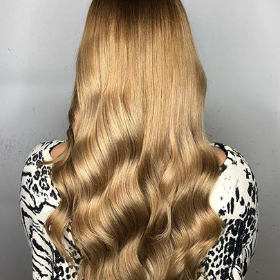 Model with long dark blonde hair with a caramel tone, created with Wella Professionals