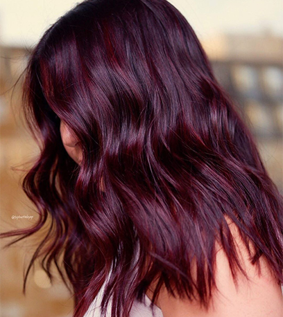 Side profile of woman with dark purple, wavy hair, created using Wella Professionals.