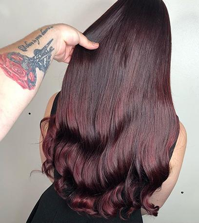 Back of woman's head with sleek dark purple hair, created using Wella Professionals.
