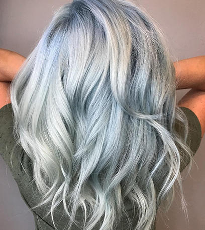 Woman with long wavy light denim blue hair using Koleston Perfect