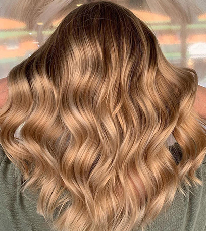 Back of woman's head with long, golden blonde, wavy hair, created using Wella Professionals.