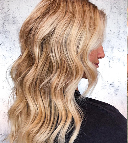 Side profile of woman with long, beachy, golden blonde hair, created using Wella Professionals.