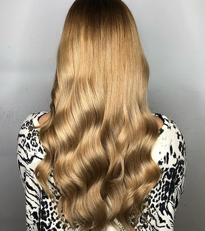 Back of woman's head with long, loosely curled, golden blonde hair, created using Wella Professionals.