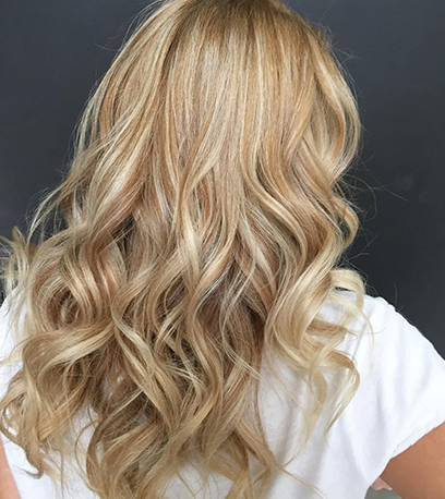 Back of woman's head with long, satin golden blonde hair, created using Wella Professionals.