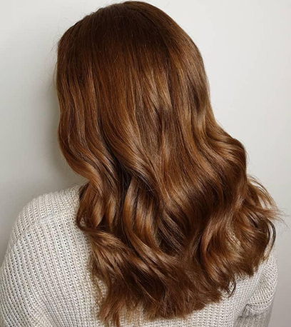 Back of woman's head with long, wavy, vintage brown hair, created using Wella Professionals.