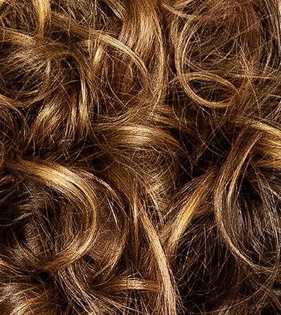 Close-up of golden brown, curly hair, created using Wella Professionals.