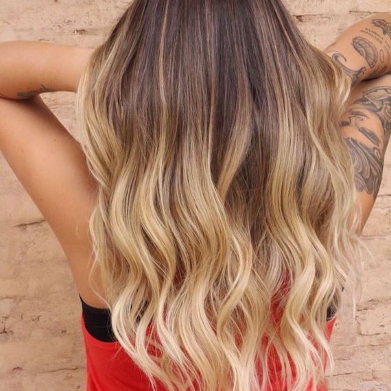 Back of woman's head with wavy hair and honey blonde balayage, created using Wella Professionals.