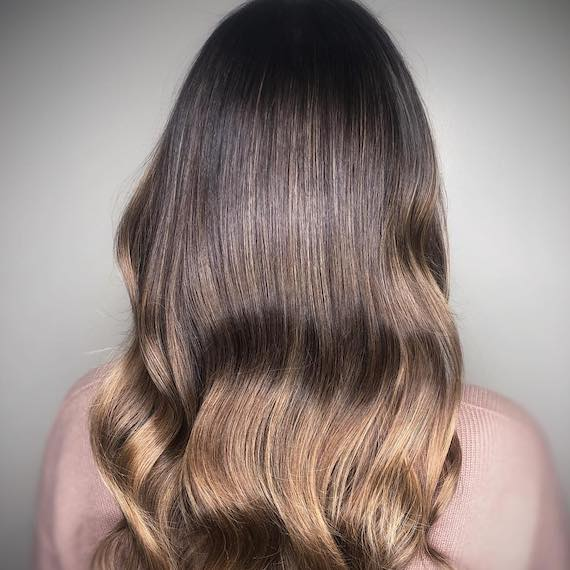 Back of woman's head with wavy dark hon-ey hair, created using Wella Professionals.