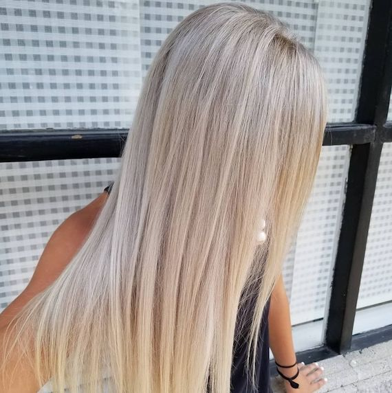 Woman with long straight ice blonde hair using Wella Professionals Color Touch